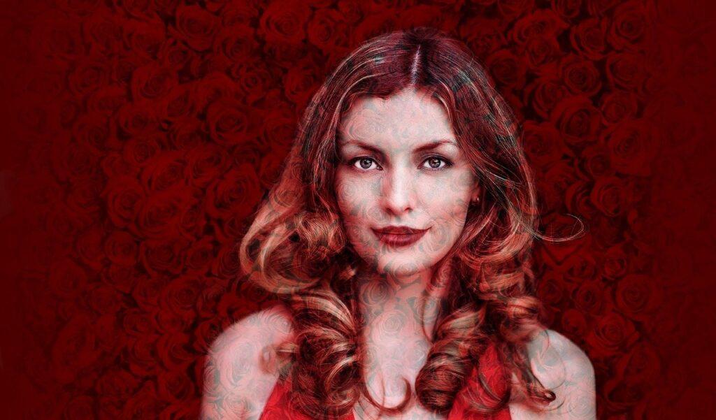 10 saveta kako da budemo kao žena na slici. Crvenokosa srećna žena okružena ružama.
